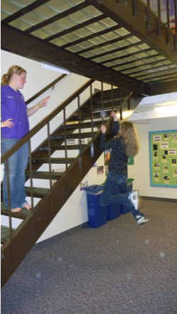 Student hangs from stair railings in Sheehan Hall.